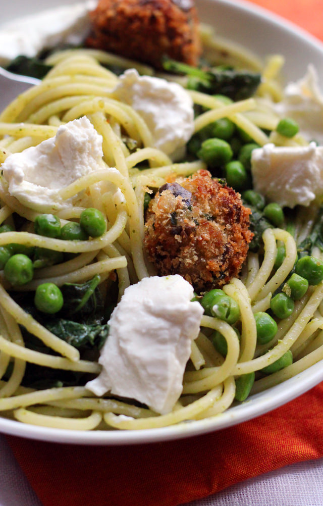 spaghetti with eggplant balls, pesto, peas, and greens